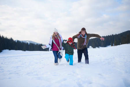 family outside: happy young  family playing in fresh snow  at beautiful sunny winter day outdoor in nature