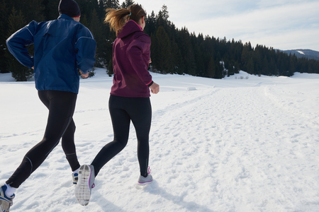 healthy young couple jogging outside on snow in forest. athlete running on  beautiful sunny winter day Stock Photo