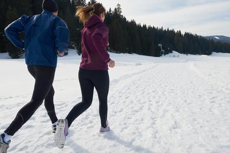 personas trotando: joven pareja sana trotar al aire libre en la nieve en el bosque. atleta corriendo en hermoso d�a soleado de invierno