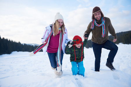 christmas winter: happy young  family playing in fresh snow  at beautiful sunny winter day outdoor in nature