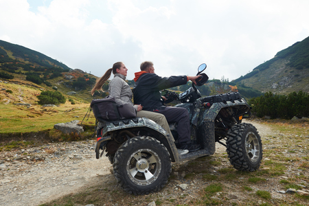 quad: couple drive atv quad bike in mountain nature Stock Photo