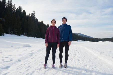 male athlete: healthy young couple jogging outside on snow in forest. athlete running on  beautiful sunny winter day Stock Photo