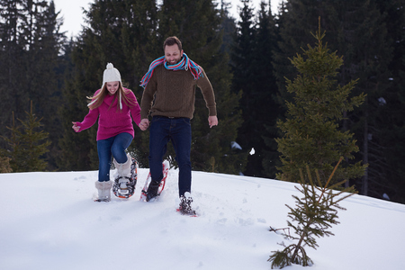 couple having fun: happy young  couple having fun and walking in snow shoes outdoor in nature at beautiful winter day. Health sport and relaxation Stock Photo