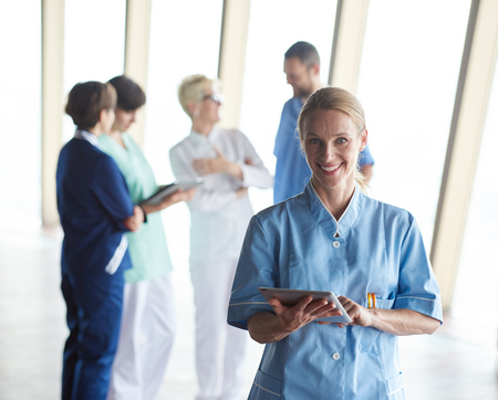 personas saludables: female doctor with tablet computer  standing in front of team  in background, group of medical staff at hospital