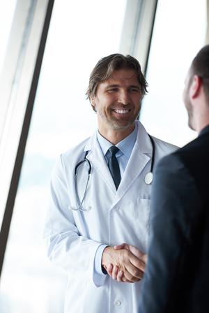 uniformes de oficina: médico apretón de manos con un paciente en los médicos luminosa oficina moderna en el hospital