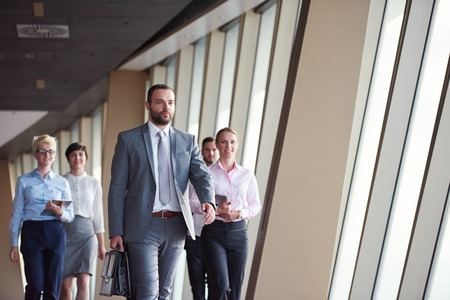 colleagues: business team, businesspeople  group walking at modern bright office interior Stock Photo