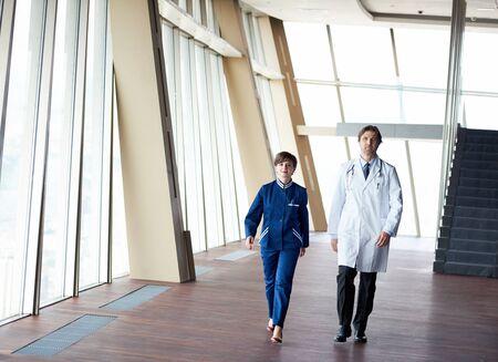 man doctor: doctors team walking in modern hospital corridor indoors, poeople group Stock Photo