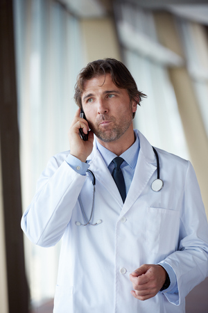 handsome doctor: handsome doctor speaking on cellphone at modern hospital indoors Stock Photo