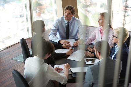 gente reunida: vista superior del grupo de hombres de negocios en la reunión, que trabajan en la oficina moderna brillante cubierta con tablet PC