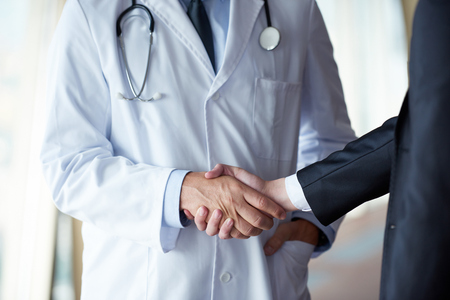 business in hand: doctor handshake with a patient at doctors bright modern office in hospital Stock Photo