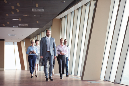 people in office: business team, businesspeople  group walking at modern bright office interior Stock Photo