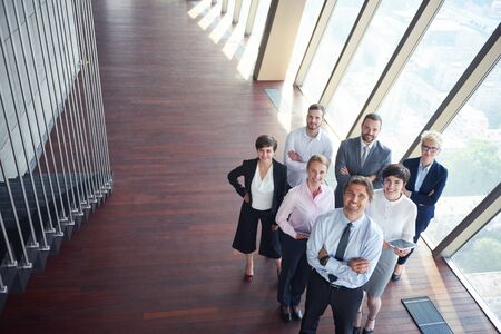 happy worker: diverse business people group standing together as team  in modern bright office interior