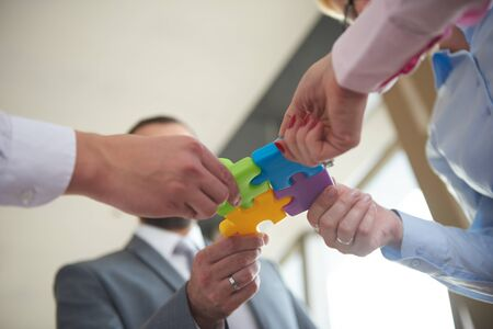 business support: business people group assembling jigsaw puzzle and represent team support and help concept, top view perspective at modern bright office interior
