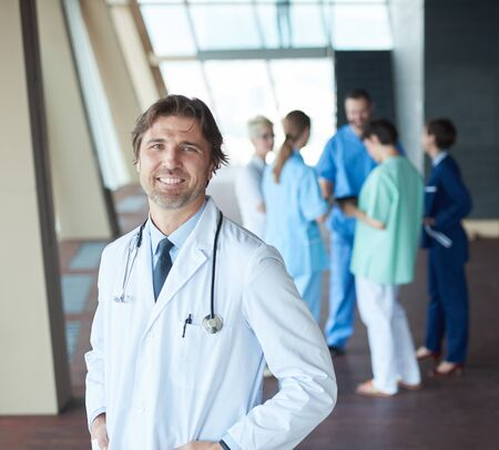 personas saludables: group of medical staff at hospital, handsome doctor in front of team, people group  standing together in background Foto de archivo