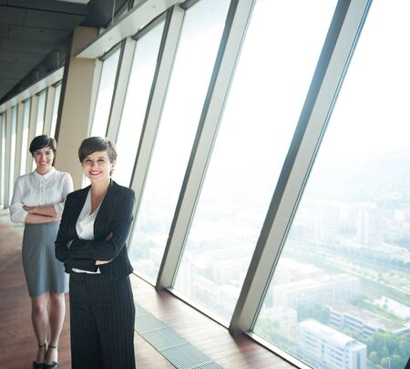 office interior: business people group,  females as team leaders standing together  in modern bright office interior