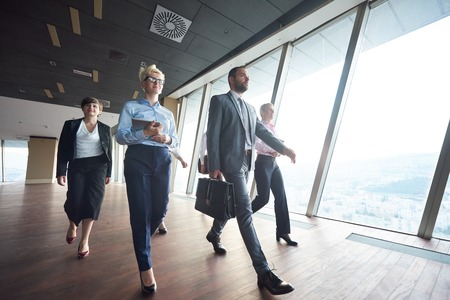 going: business team, businesspeople  group walking at modern bright office interior Stock Photo