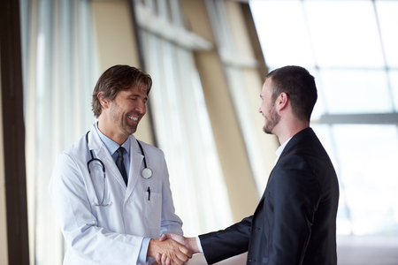 office visit: doctor handshake with a patient at doctors bright modern office in hospital Stock Photo