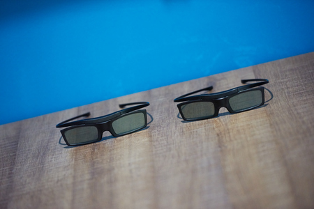 three dimensions: hi technology modern movie 3d glasses with blue background