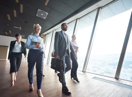 ビジネス チームは、モダンな明るいオフィスのインテリアに歩くビジネスマン グループ