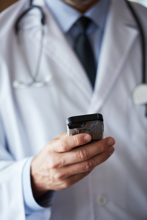holding cell: handsome doctor speaking on cellphone at modern hospital indoors Stock Photo