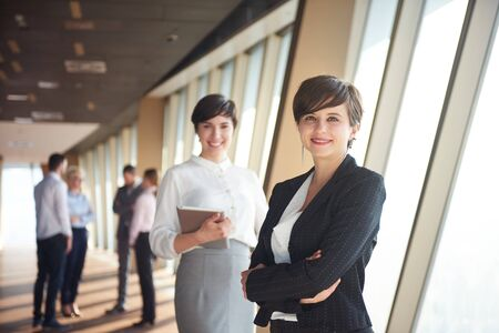 work together: business people group,  females as team leaders standing together  in modern bright office interior