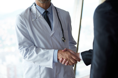 doc: doctor handshake with a patient at doctors bright modern office in hospital Stock Photo