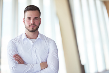 guy portrait: portrait of happy young handsome hipster business man with beard at modern office space interior