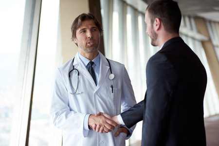 men shaking hands: doctor handshake with a patient at doctors bright modern office in hospital Stock Photo
