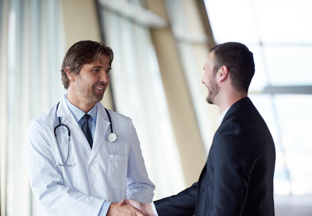 doctor handshake with a patient at doctors bright modern office in hospital Banque d'images