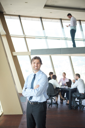 businesspeople: handosme business manportrait  at modern bright office indoors with his team in group working together in background Stock Photo