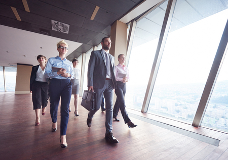 businesspeople: business team, businesspeople  group walking at modern bright office interior Stock Photo