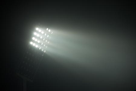 stade de football feux des réflecteurs sur le fond noir