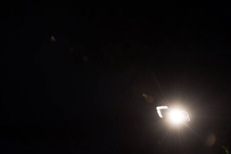 xenon: driving car in night,  modern front lights lens flare in black background Stock Photo