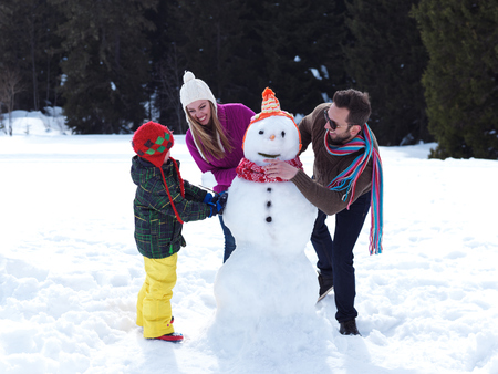 making fun: happy young  family playing in fresh snow and making snowman at beautiful sunny winter day outdoor in nature with forest in background