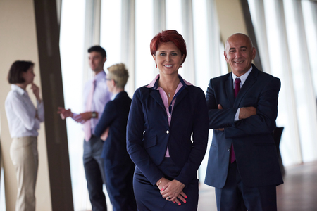 red hair girl: diverse business people group standing together as team  in modern bright office interior  with redhair senior woman in front as leader Stock Photo