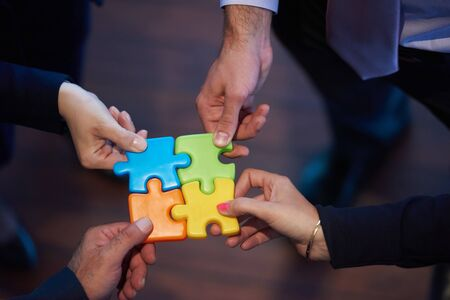 business help: business people group assembling jigsaw puzzle and represent team support and help concept, top view perspective at modern bright office interior
