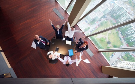 glass table: top view of  business people group on meeting throwing documents in air
