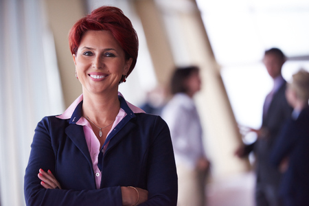executive woman: Smilling young business woman in front her team blured in background. Group of young business people. Modern bright  startup office interior. Stock Photo