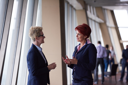 two women: portrait  of two corporate business woman at modern bright office interior standing in group as team Stock Photo