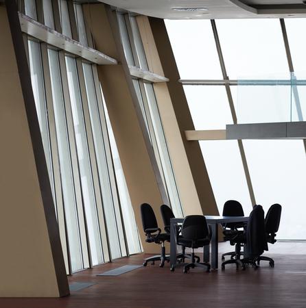会議室白いモダンなテーブルと、ガラスの壁とオレンジ色の椅子