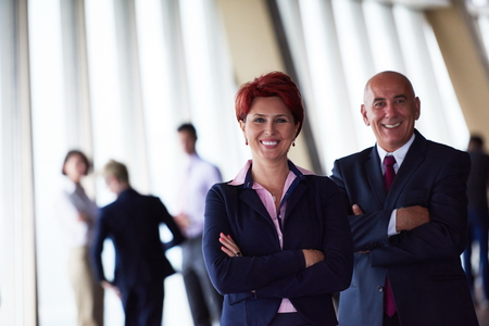 woman business suit: diverse business people group standing together as team  in modern bright office interior  with redhair senior woman in front as leader Stock Photo
