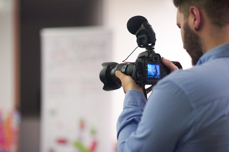 videographer at conference seminar taking footage and recording video on camera