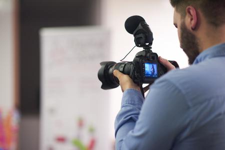 Videograaf op conferentie seminar nemen van beelden en video-opname op de camera Stockfoto - 48956350