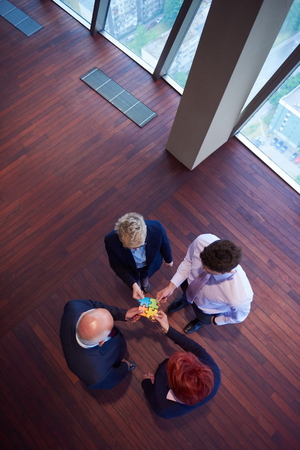 business concept: business people group assembling jigsaw puzzle and represent team support and help concept, top view perspective at modern bright office interior