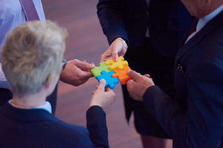 groups of people: business people group assembling jigsaw puzzle and represent team support and help concept, top view perspective at modern bright office interior