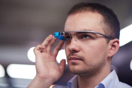 futuristic man: young man using virtual reality gadget computer technology glasses