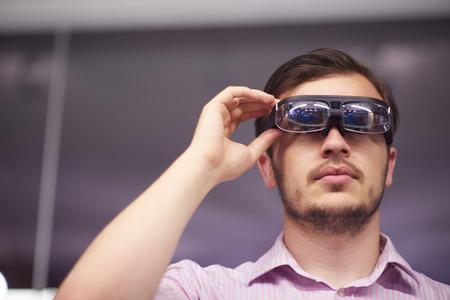 virtual technology: young man using virtual reality gadget computer technology glasses