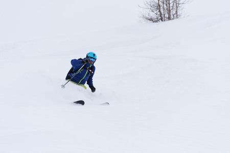 off piste: extreme freeride skier skiing on fresh powder snow in forest downhill at winter season Stock Photo