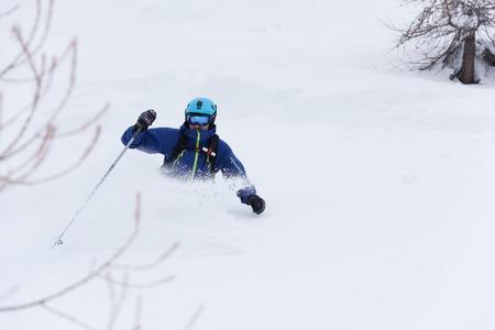 powder snow: extreme freeride skier skiing on fresh powder snow in forest downhill at winter season Stock Photo