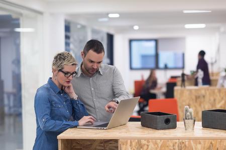 equipo de negocios de inicio en el cumplimiento de moderno y luminoso de reflexión interior de la oficina, trabajando en equipo portátil y la tableta de ordenador